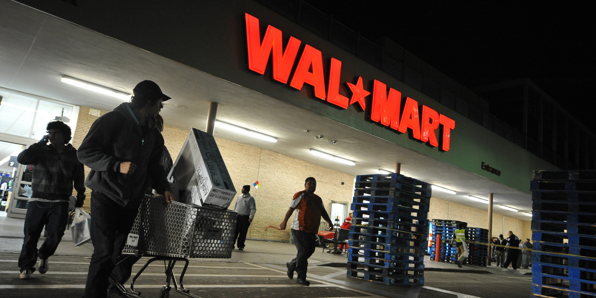 Shoppers wheel their purchases out of a Wal-Mart store in Los Angeles, California, before dawn on Black Friday, November 27, 2009. The annual sales bonanza is held one day after the Thanksgiving holiday. AFP PHOTO / Robyn Beck (Photo credit should read ROBYN BECK/AFP/Getty Images)